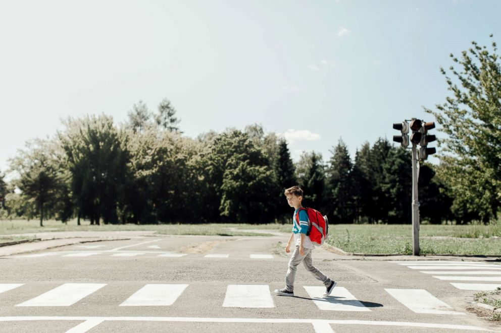 A young boy crosses the street.