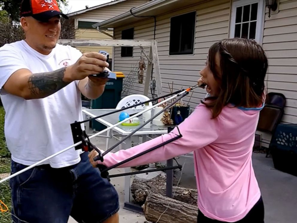 PHOTO: Jason McDonald films his daughter Alexis as she readies the slingshot that she is using as a way of removing one of her last few baby teeth.