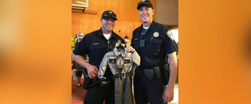 PHOTO: Santa Rosa police officers hold a Halloween costume given away to a child at the Santa Rosa Police Departments costume giveaway.