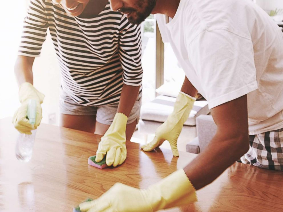 PHOTO: A young couple clean the surface of a table in an undated stock photo.