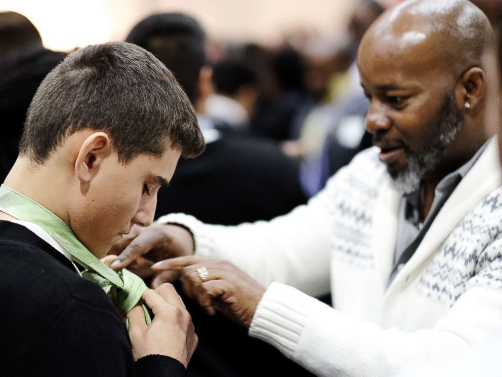 PHOTO: A mentor teaches a student to tie a tie at Billy Earl Dade Middle Schools Breakfast with Dads event on Dec. 14, 2017.