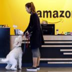 An Amazon employee gives her dog a biscuit as the pair head into a company building, where dogs are welcome, in Seattle, Oct. 11, 2017.