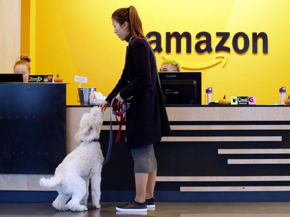 PHOTO: An Amazon employee gives her dog a biscuit as the pair head into a company building, where dogs are welcome, in Seattle, Oct. 11, 2017.