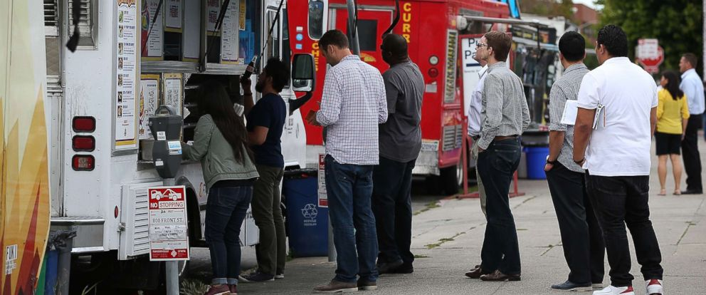 PHOTO: Customers line up to order food from food trucks on July 7, 2014 in San Francisco.