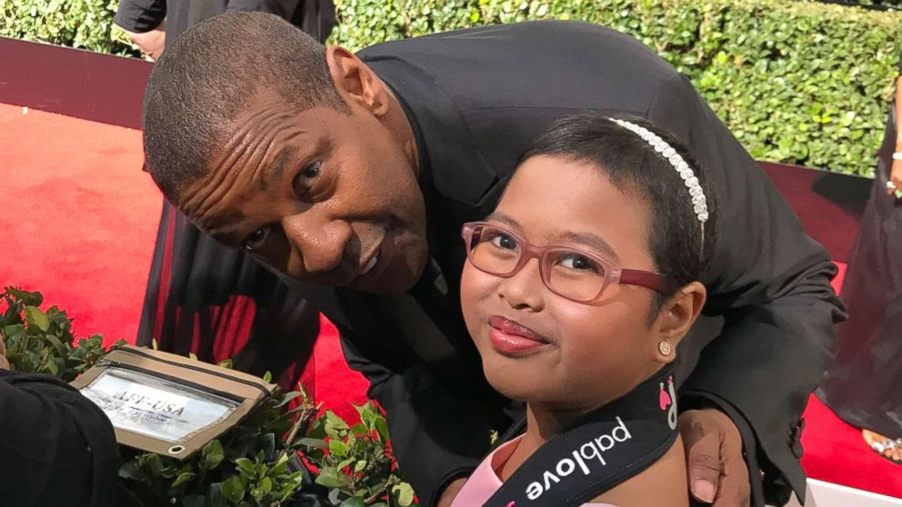 Francine Gascon, 10, poses with Denzel Washington as she takes photos of stars on the Golden Globes red carpet.