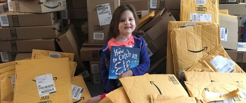 "PHOTO: Lena Tietjen, 4, with a pile of books delivered for her ""library."""
