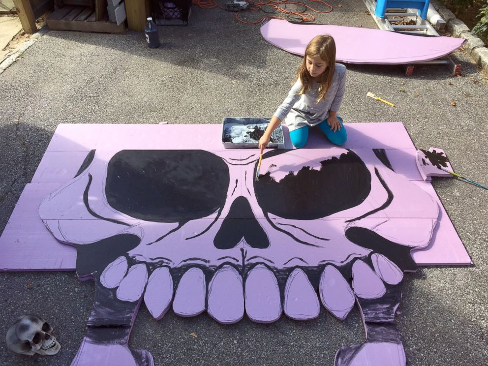 PHOTO: Michael Frys eldest daughter Eily helping paint their giant skull decoration in 2016.