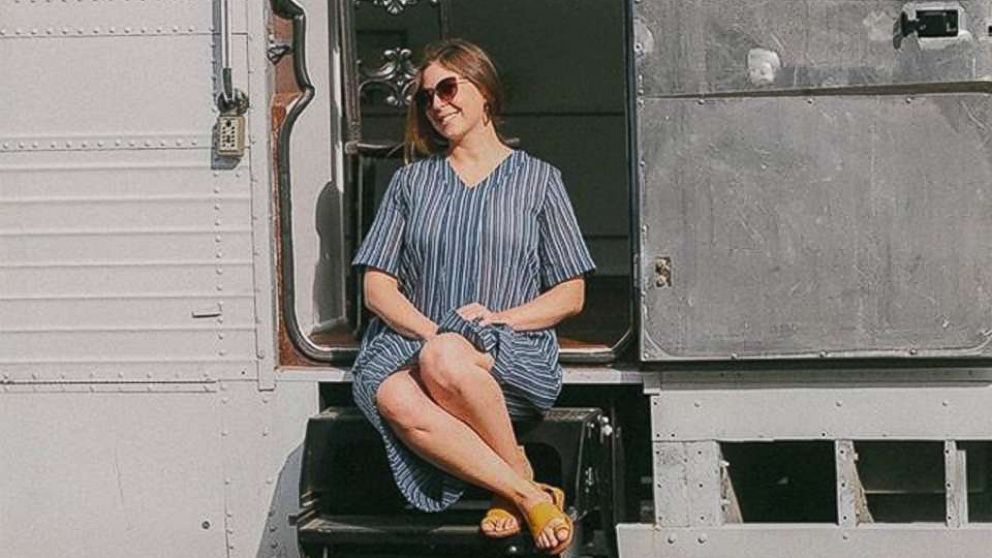 Jessie Lipskin sits on the steps of the chic RV she converted from a Greyhound bus.