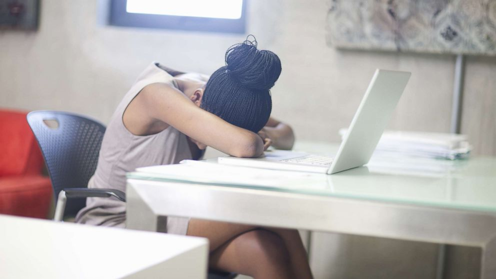 A woman puts her head down at work in an undated stock photo.