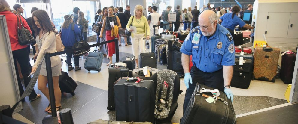 PHOTO: A TSA agent checks luggage as passengers arrive for flights at OHare International Airport on May 23, 2014 in Chicago, Ill.