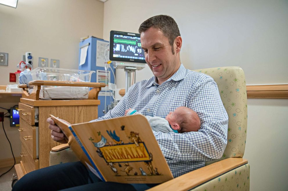 PHOTO: Brad Curran reads a donated book to his son in the neo-natal intensive care unit at UPMC Magee-Womens Hospital.
