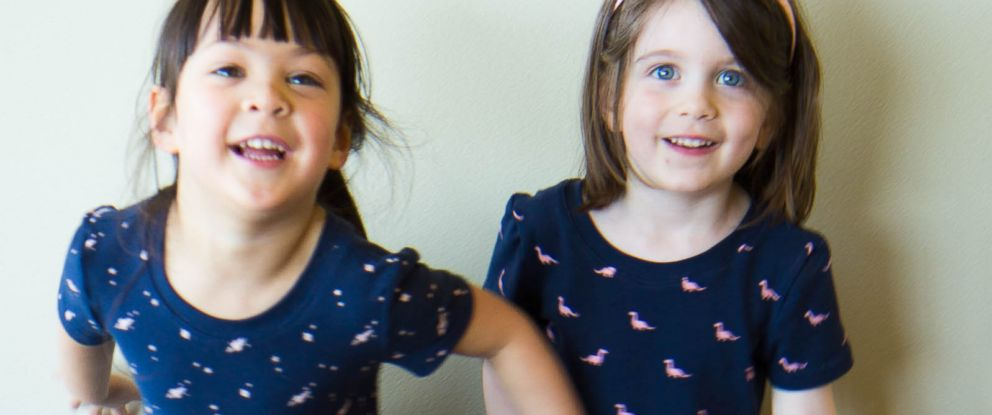 PHOTO: Two girls model the rocket ship print dress and the dinosaur print dress by buddingSTEM.