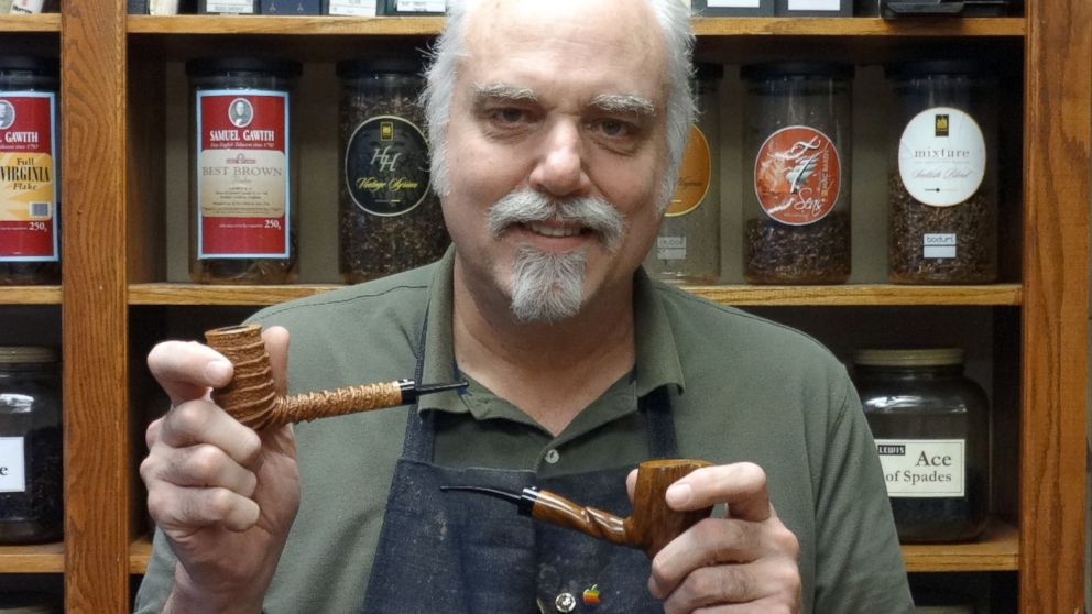 Minneapolis pipe maker Richard Lewis shows off two of the pipes he makes and sells at Lewis Pipe and Tobacco.
