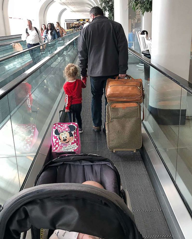 PHOTO: Todd Walker, 52, of Lenexa, Kansas, seen on April 10 walking through the airport in Charlotte, North Carolina, with Caroline Rudeen, 3.