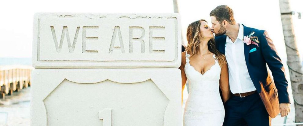 PHOTO: Jaylyn and Brian Moogan kiss next to a sand sculpture promoting tourism to the Florida Keys on their wedding day at Casa Marina on Key West, Oct. 14, 2017. They were the first couple married at the Waldorf Astoria resort since Hurricane Irma.
