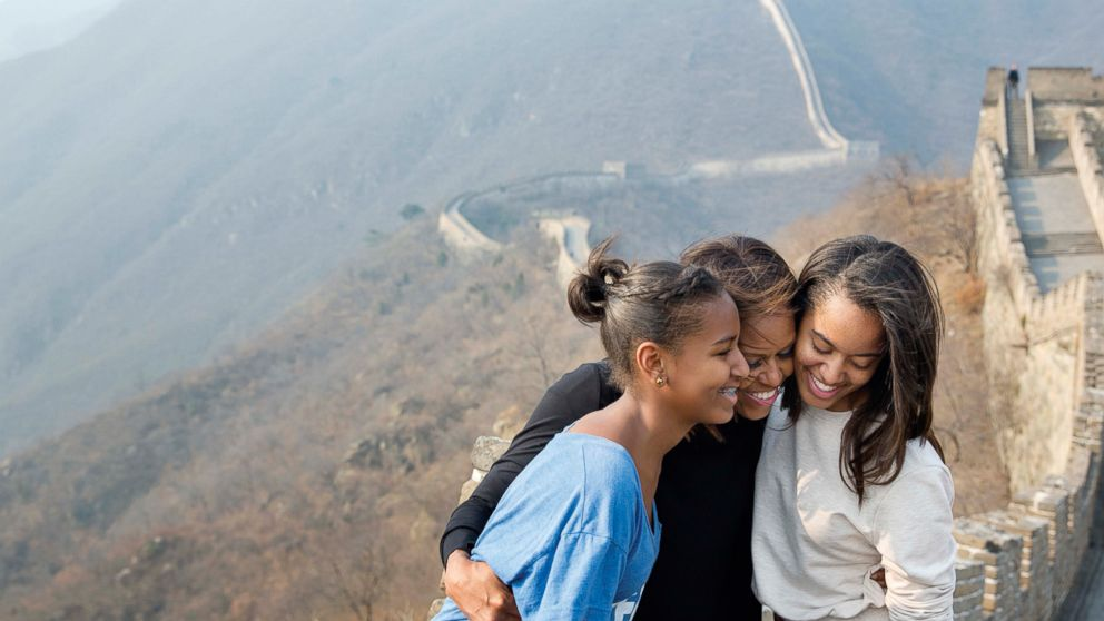 The First Lady hugs her daughters Sasha and Malia as they visit the Great Wall of China in Mutianyu, China, March 23, 2014.