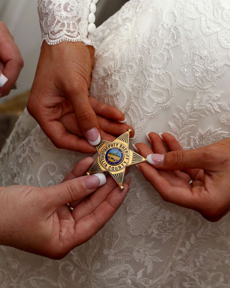 PHOTO: Mikayla Wroten of Crown City, Ohio, holds her fathers badge on her Oct. 14 wedding day.