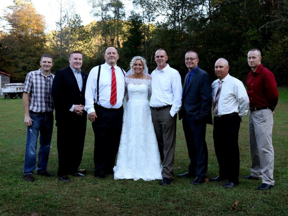 PHOTO: Mikayla Wroten poses with her fathers former police colleagues after they surprised her with wedding dances.