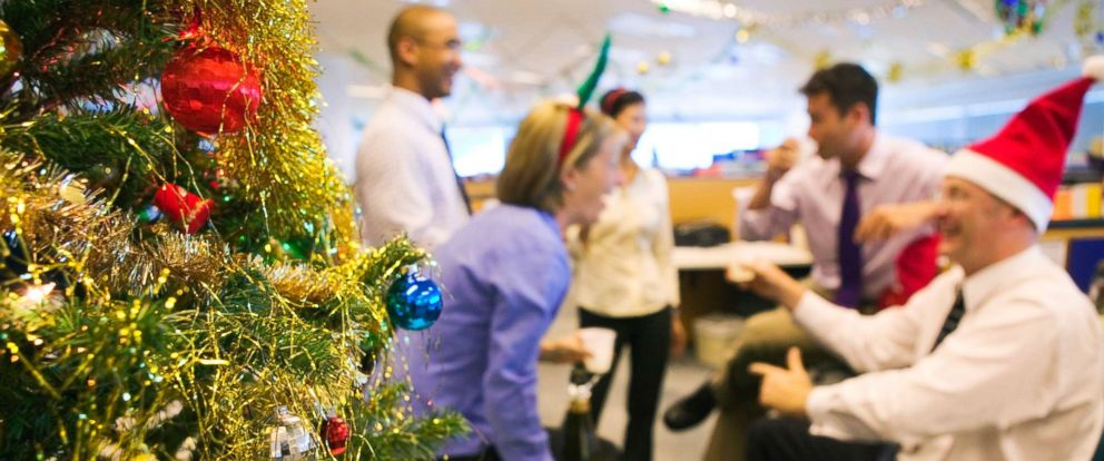 PHOTO: Coworkers chat at a holiday office party.