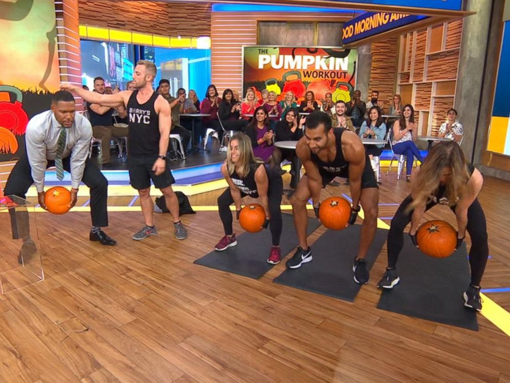 PHOTO: Good Morning America co-anchor Michael Strahan does squats alongside trainers from Barrys Bootcamp in a Halloween pumpkin workout.