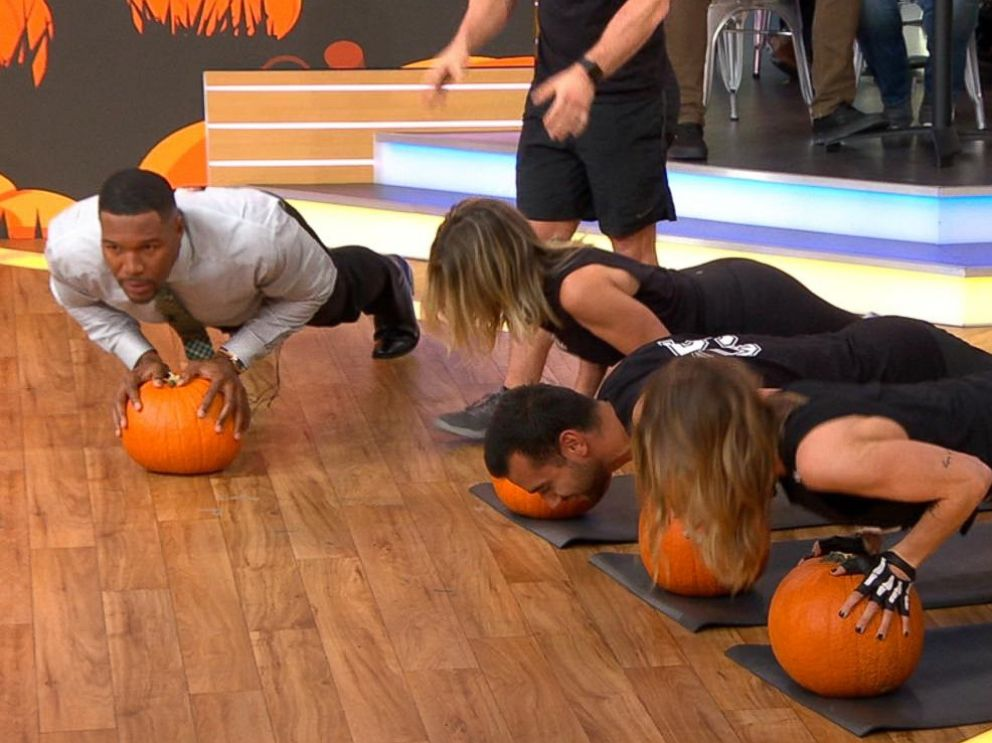 PHOTO: Good Morning America co-anchor Michael Strahan does pushups using a pumpkin with trainers from Barrys Bootcamp.