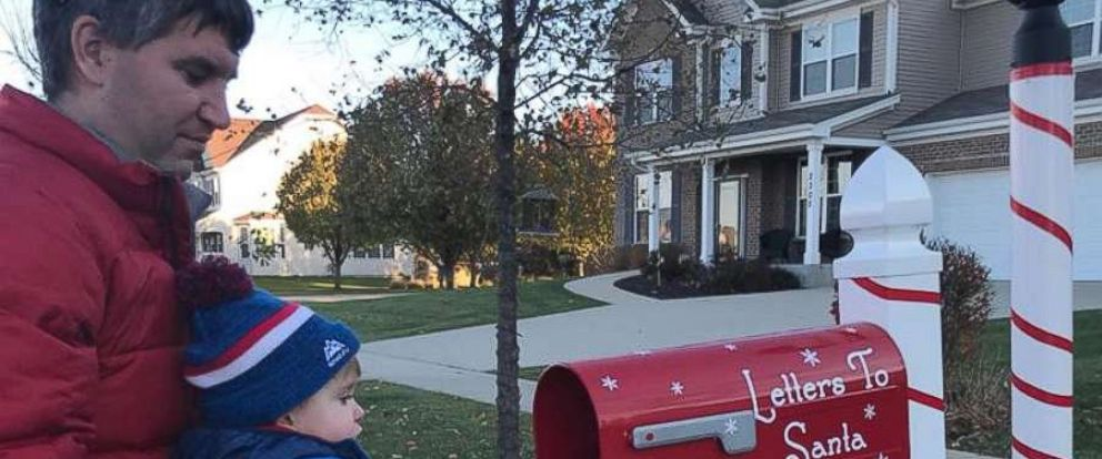 PHOTO: Austin Falli drops off his letter with his daddy holding him up to the mailbox.