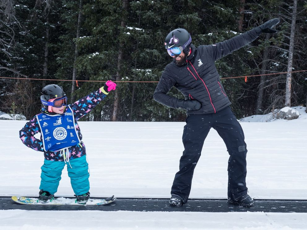 PHOTO: Lilly Biagini, 10, snowboards alongside U.S. Paralympian Keith Gabel.