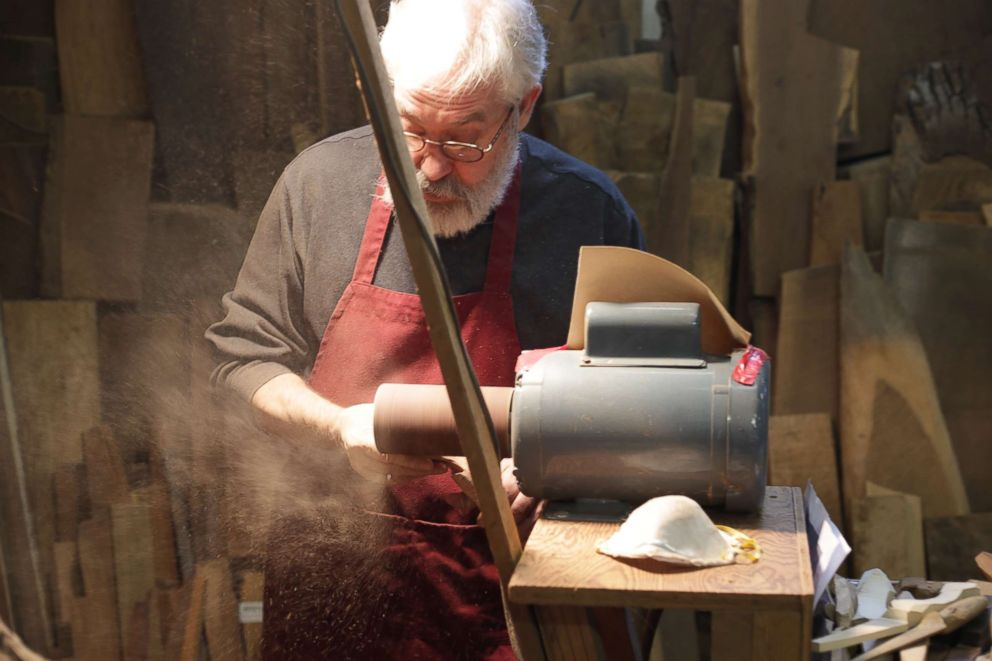 PHOTO: Woodworker Norm Sartorius sanding an abstract wooden spoon.