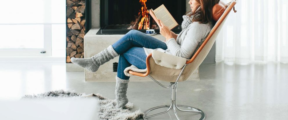 PHOTO:An undated stock photo of woman reading a book in front of fireplace in Sweden.
