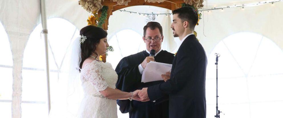 PHOTO: Jennifer Jensen, 24, and Bill Jensen, 27, hold hands before Judge Chris Wilton at their wedding.