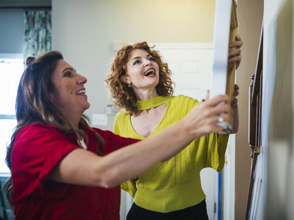 PHOTO: Laurie Smith hangs a piece of art with a homeowner on Trading Spaces.