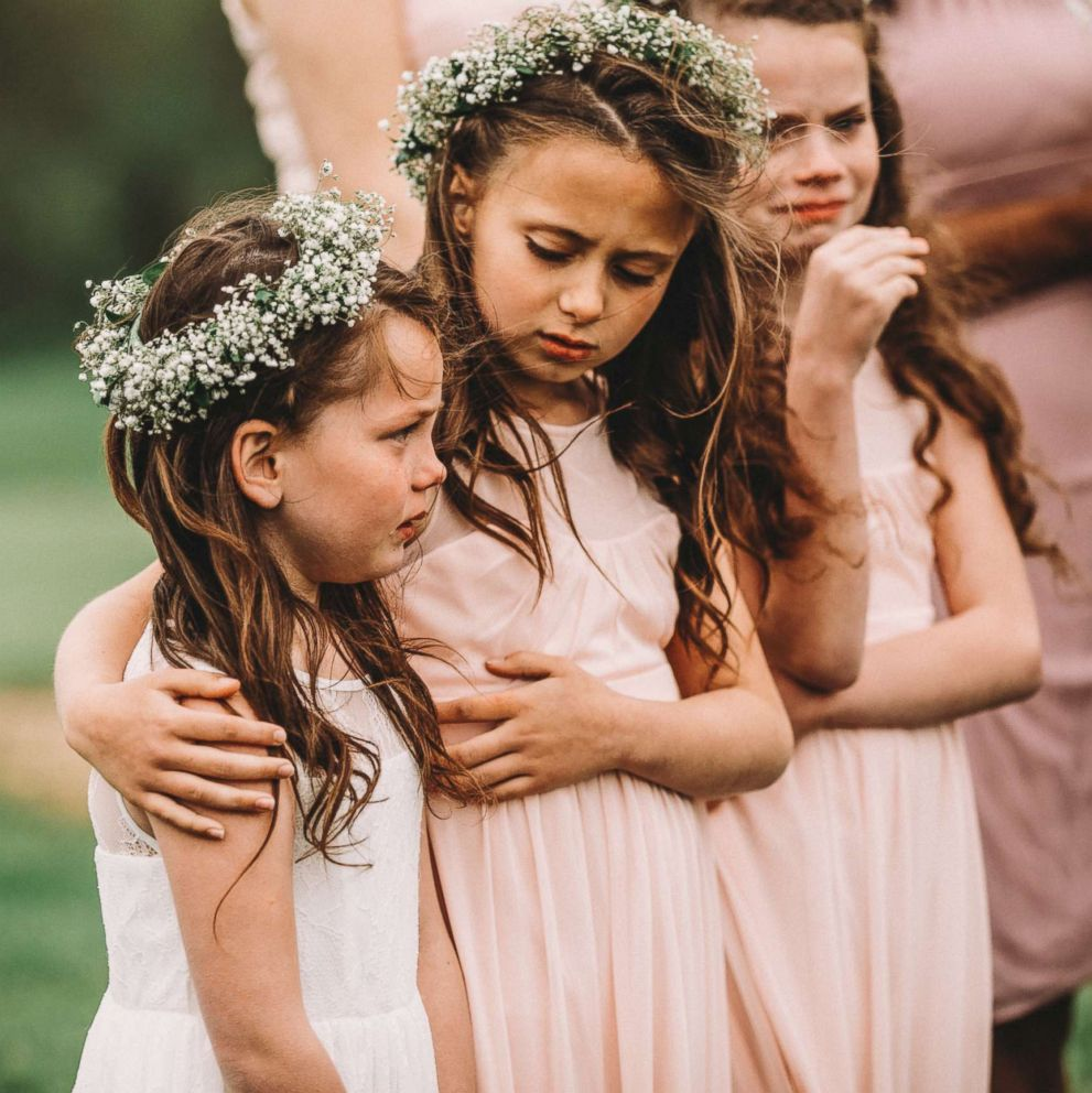 PHOTO: Riley Gibson, 8, comforts her sister Lexi, 6, on May 12 at their parents wedding in Iowa.