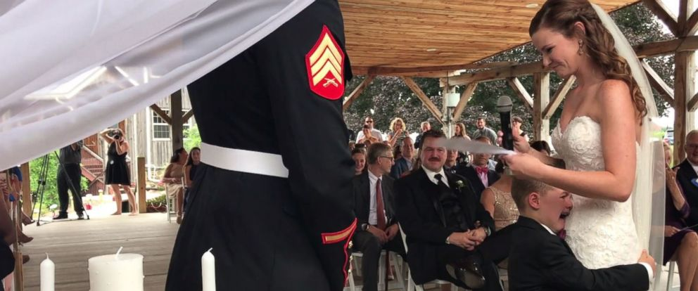 PHOTO: USMC Sergeant Joshua Newville and his bride Senior Airman Emily Leehan shared a special moment with his son Gage, 4, as she recited her vows.