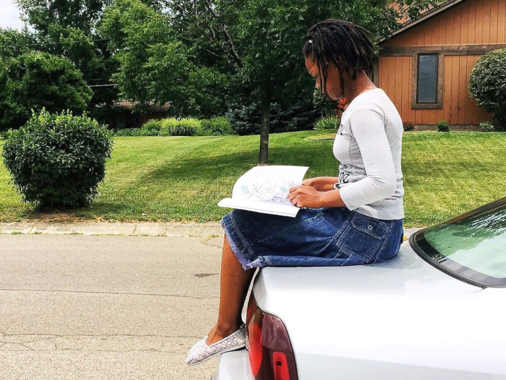 PHOTO: Nakiah White, 12, reads a book outside.
