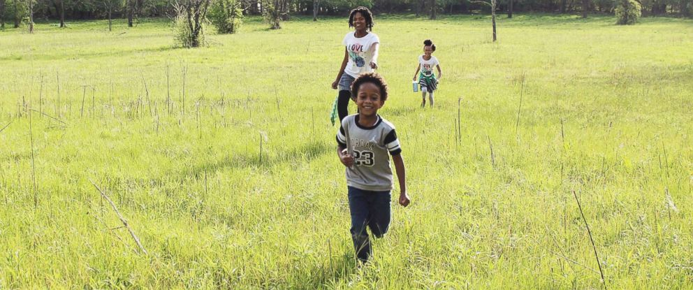 PHOTO: Samuel White, 7, Nakiah White, 12, and Ava White, 10, run outside together.