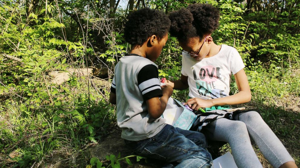 Samuel White, 7, and Ava White, 10, study together in the outdoors.