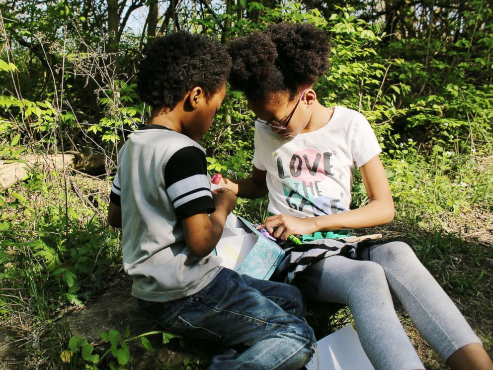 PHOTO: Samuel White, 7, and Ava White, 10, study together in the outdoors.