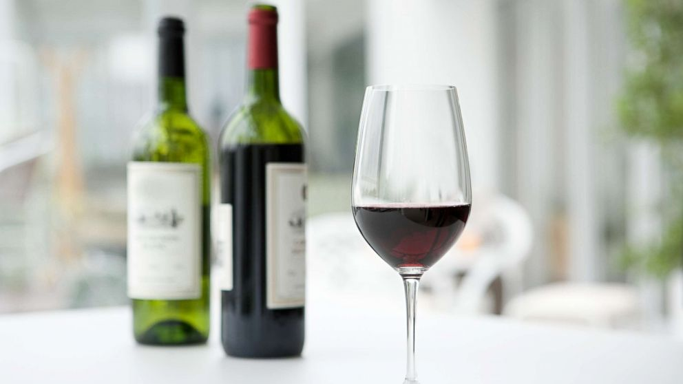 In this undated stock photo is a glass of red wine in front of bottles of wine.