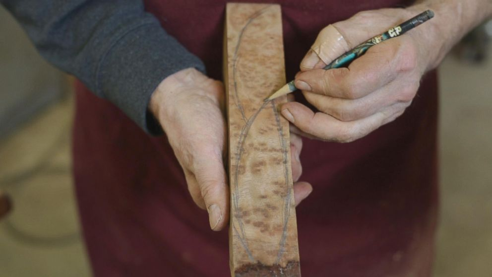 Woodworker Norm Sartorius sketching out an outline of a spoon on a plank of wood.