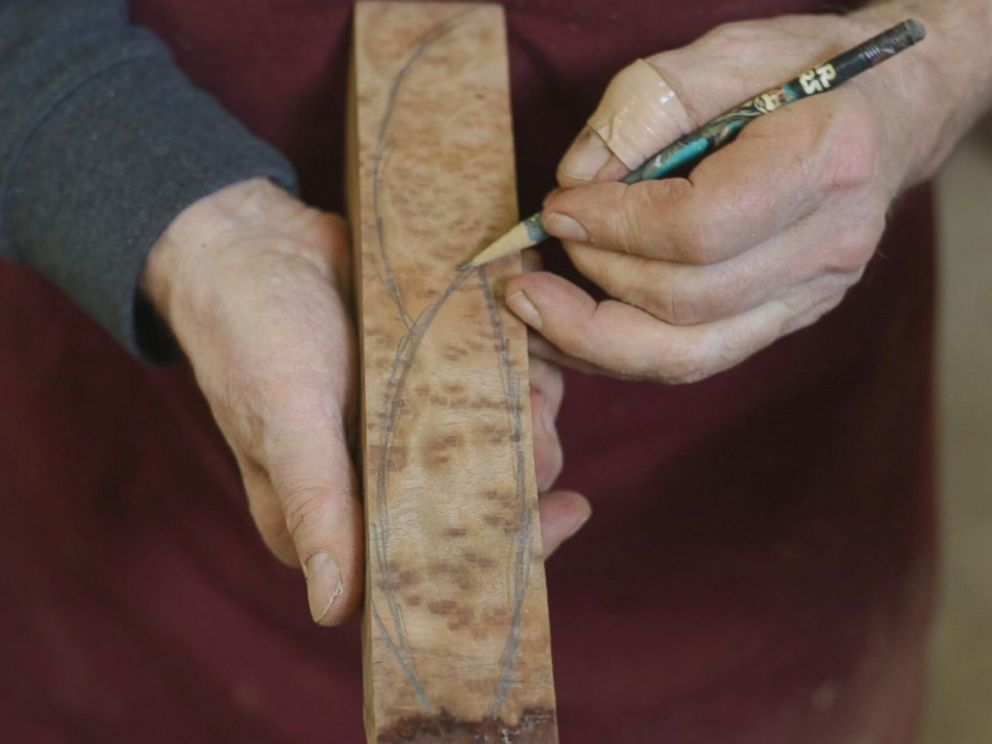 PHOTO: Woodworker Norm Sartorius sketching out an outline of a spoon on a plank of wood.