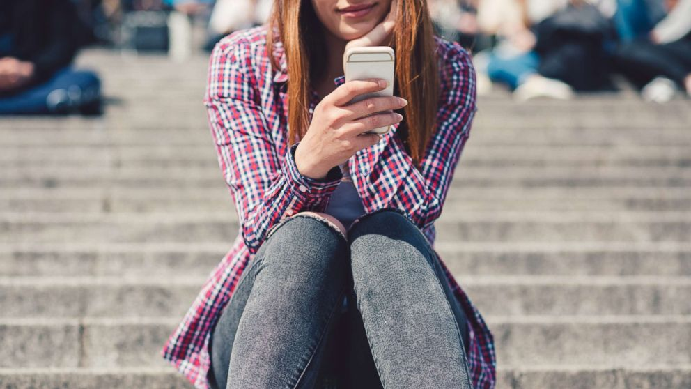 In this undated stock photo, a young woman sitting on the stairs while she is text messaging.