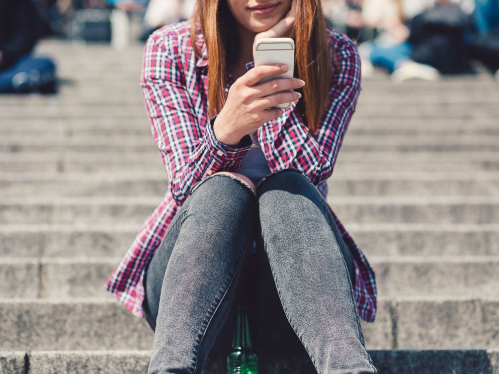PHOTO: In this undated stock photo, a young woman sitting on the stairs while she is text messaging.