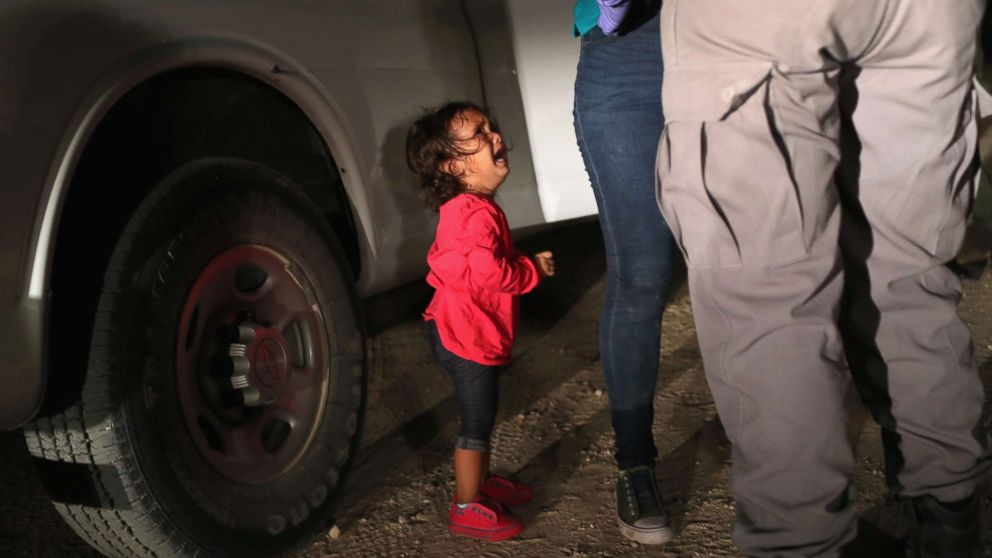 """A two-year-old Honduran asylum seeker cries as her mother is searched and detained near the U.S.-Mexico border on June 12, 2018, in McAllen, Texas. The asylum seekers had rafted across the Rio Grande from Mexico and were detained by U.S. Border Patrol agents before being sent to a processing center for possible separation. Customs and Border Protection (CBP) is executing the Trump administration's """"zero tolerance"""" policy towards undocumented immigrants."""