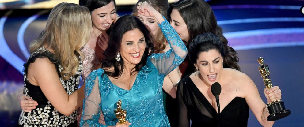 """PHOTO: Melissa Berton (center L) and Rayka Zehtabchi, center right, accepts the Documentary (Short Subject) award for """"Period. End of Sentence."""" onstage during the 91st Annual Academy Awards at Dolby Theatre, Feb. 24, 2019, in Hollywood, Calif."""