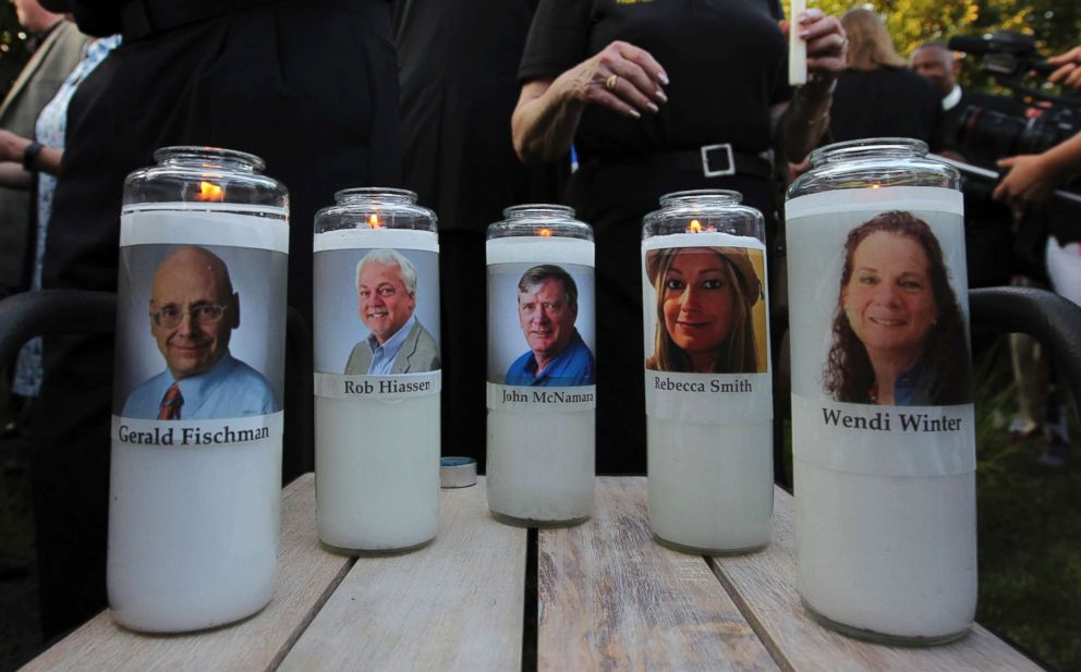 PHOTO: Photos of five journalists adorn candles during a vigil across the street from where they were slain in their newsroom in Annapolis, Md., June 29, 2018.