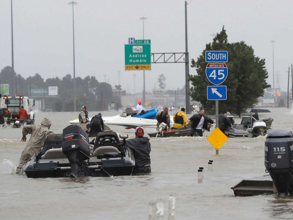 PHOTO: Volunteer rescue boats make their way into a flooded subdivision to rescue stranded residents as floodwaters from Tropical Storm Harvey rise, Aug. 28, 2017, in Spring, Texas.