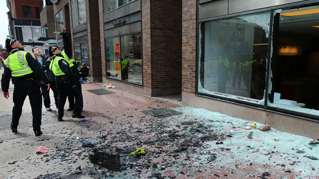 PHOTO: Boston Police look at blown out windows at the scene near the finish line of the Boston Marathon, April 15, 2013.