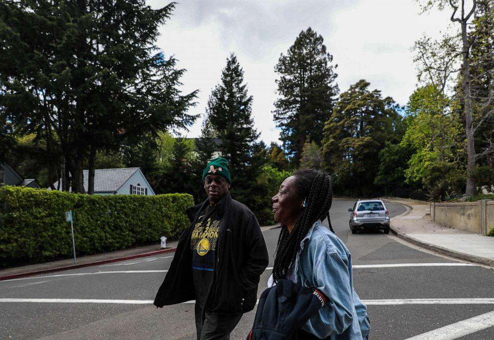 PHOTO: Greg Dunston, Sr. and his partner Marie Mckinzie walk back home after visiting Hampton Park, in Piedmont, Calif., on April 16, 2019.
