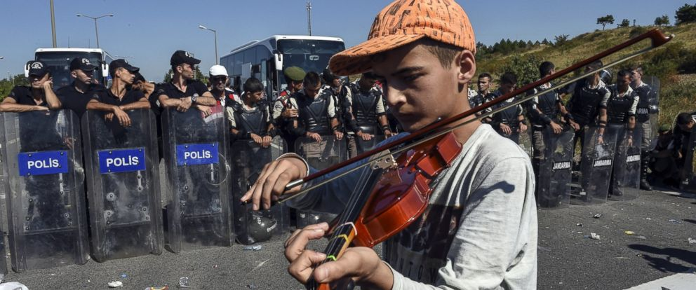 PHOTO: Alameddin, a 13-year-old Syrian boy, plays the violin in front of a police barricade as he marches toward the border between Turkey and Greece with other refugees, in Turkey, Sept. 19, 2015.