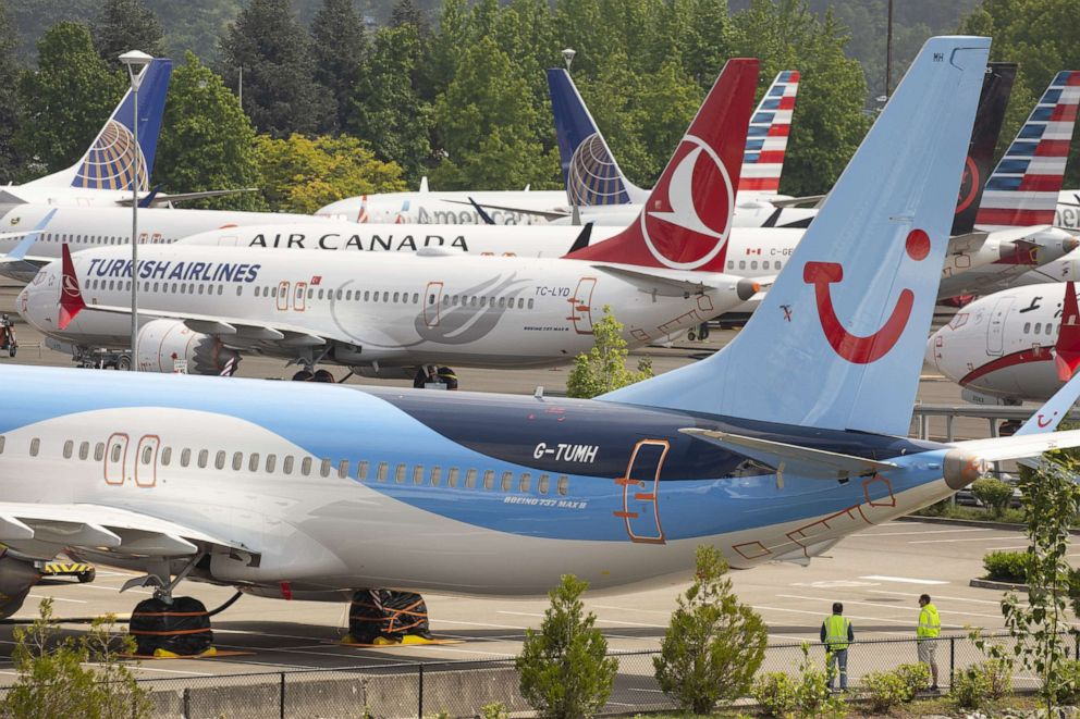 PHOTO: Workers stand near Boeing 737 MAX airplanes as they sit parked at a Boeing facility adjacent to King County International Airport, known as Boeing Field, on May 31, 2019, in Seattle.